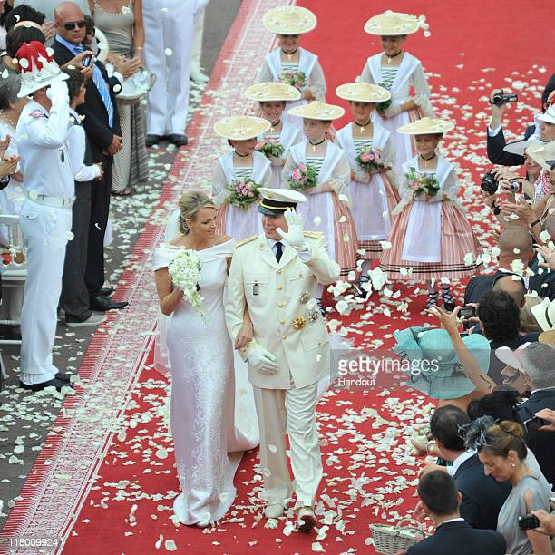 In this handout image provided by the Palais Princier Princess Charlene of Monaco and Prince Albert II of Monaco are showered with confetti during...