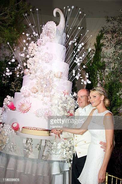 In this handout image provided by the Palais Princier Princess Charlene of Monaco and Prince Albert II of Monaco cut the cake during the religious...