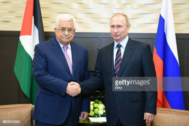 In this handout image provided by the Palestinian Press Office President Mahmoud Abbas shakes hands with Russian President Vladimir Putin during a...