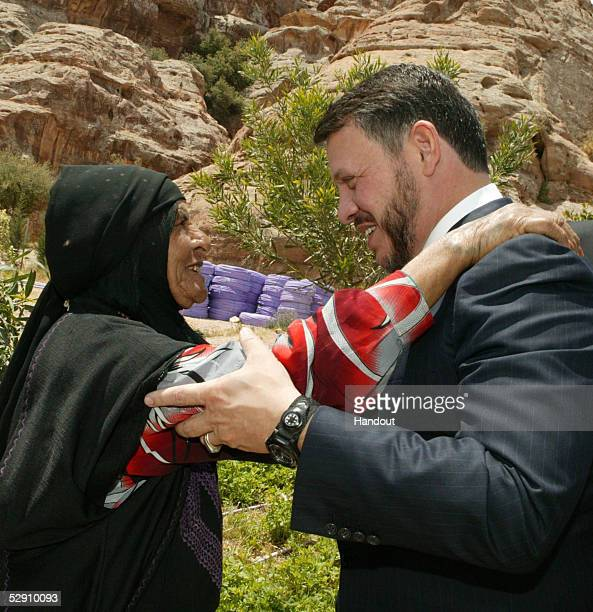 In this handout image provided by the Royal Jordanian Palace Jordan's King Abdullah greets an elderly bedouin woman during his tour of...