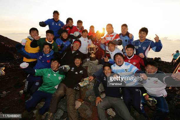 In this handout image provided by the Rugby World Cup 2019 Organising Committee climbers wearing participating countries' uniforms pose with the Webb...