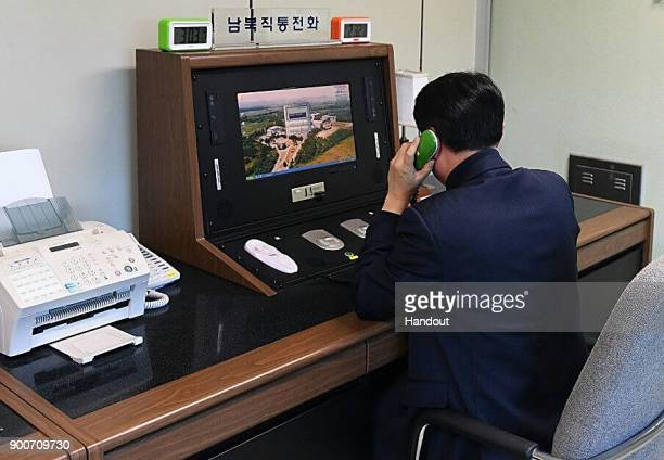 In this handout image provided by the South Korean Unification Ministry A South Korean government official checks the direct communications hotline...