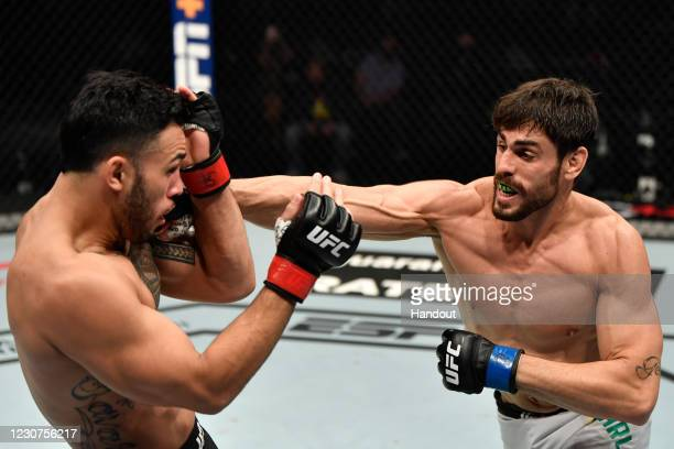 In this handout image provided by the UFC, Antonio Carlos Junior of Brazil punches Brad Tavares in a middleweight fight during the UFC 257 event...