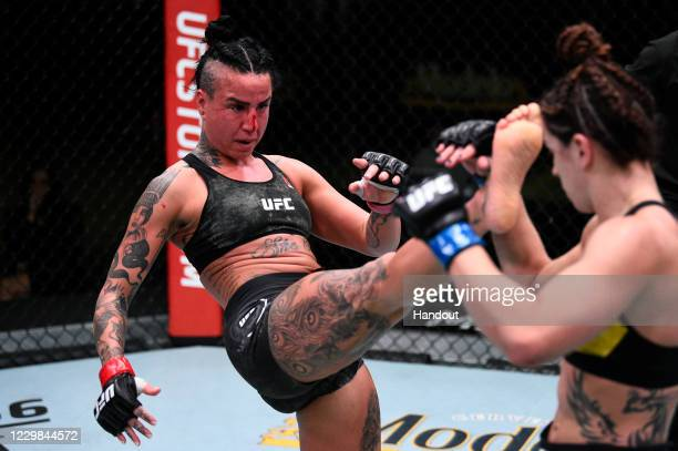 In this handout image provided by the UFC, Ashlee Evans-Smith kicks Norma Dumont of Brazil in their women's bantamweight bout during the UFC Fight...