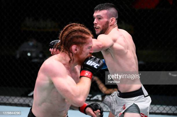 In this handout image provided by the UFC, Bill Algeo punches Spike Carlyle in their featherweight bout during the UFC Fight Night at UFC APEX on...