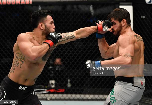 In this handout image provided by the UFC, Brad Tavares punches Antonio Carlos Junior of Brazil in a middleweight fight during the UFC 257 event...