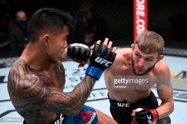 In this handout image provided by the UFC, Jonathan Pearce punches Kai Kamaka in their featherweight bout during the UFC Fight Night at UFC APEX on...