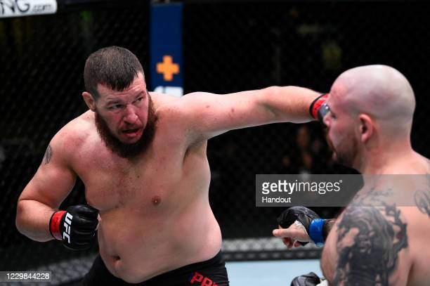 In this handout image provided by the UFC, Josh Parisian punches Parker Porter in their heavyweight bout during the UFC Fight Night at UFC APEX on...