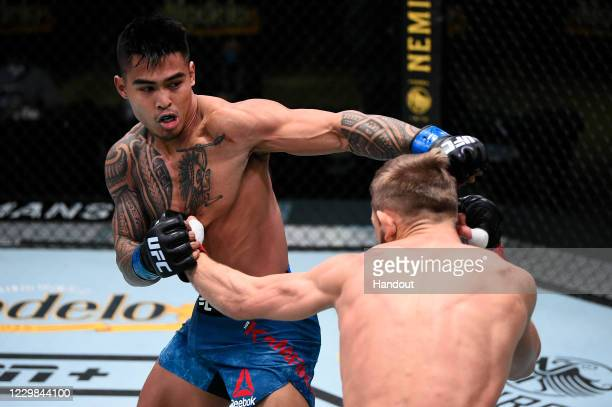 In this handout image provided by the UFC, Kai Kamaka punches Jonathan Pearce in their featherweight bout during the UFC Fight Night at UFC APEX on...