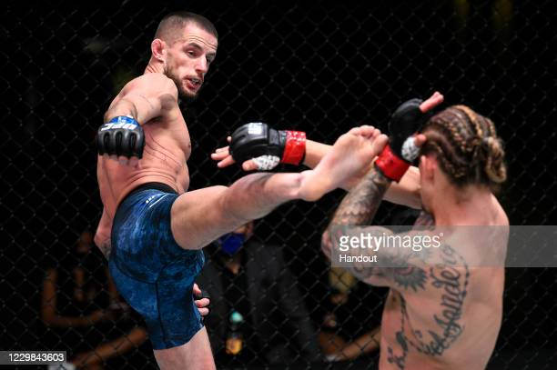 In this handout image provided by the UFC, Nate Maness kicks Luke Sanders in their catchweight bout during the UFC Fight Night at UFC APEX on...