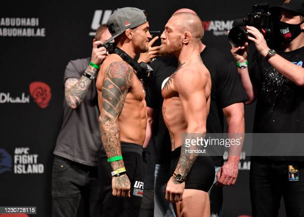 In this handout image provided by the UFC, Opponents Dustin Poirier and Conor McGregor of Ireland face off during the UFC 257 weigh-in at Etihad...