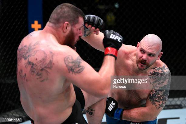 In this handout image provided by the UFC, Parker Porter punches Josh Parisian in their heavyweight bout during the UFC Fight Night at UFC APEX on...