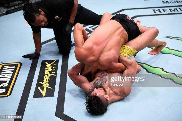 In this handout image provided by the UFC, referee Herb Dean stops the fight as Anderson dos Santos of Brazil submits Martin Day in their...