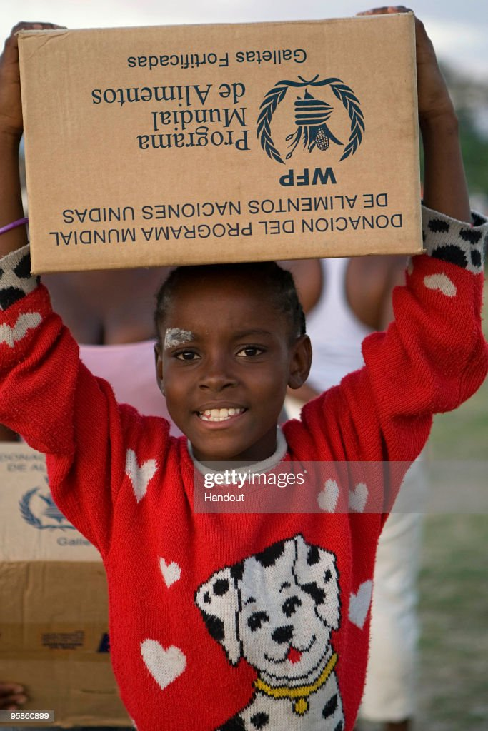 In this handout image provided by the United Nations Stabilization Mission in Haiti (MINUSTAH), a young girl smiles while carrying a box away from a UN food distribution point January 18, 2010 in Port Au Prince, Haiti. Haiti is trying to recover from a powerful 7.0-strong earthquake on January 12 that struck and devastated the country while displacing millions and killing tens of thousands.