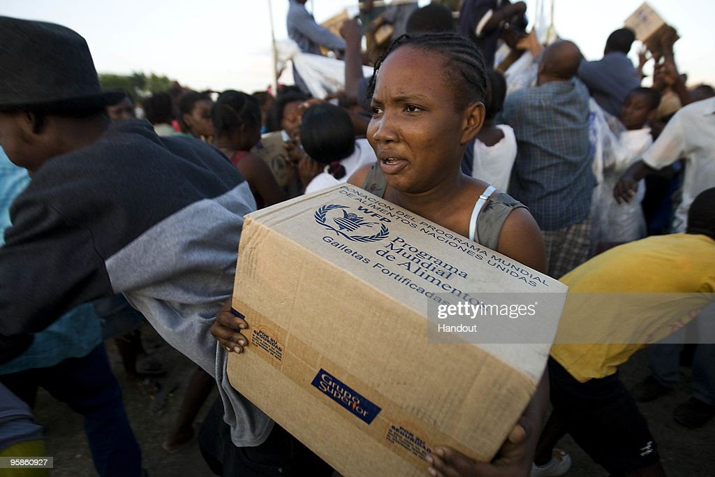 In this handout image provided by the United Nations Stabilization Mission in Haiti (MINUSTAH), a Haitian woman struggles with her box of food at a UN distribution point January 18, 2010 in Port Au Prince, Haiti. Haiti is trying to recover from a powerful 7.0-strong earthquake on January 12 that struck and devastated the country while displacing millions and killing tens of thousands.