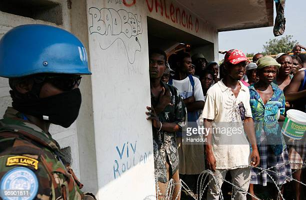 In this handout image provided by the United Nations Stabilization Mission in Haiti Haitians wait for food being distrbuted by the UN outside a...