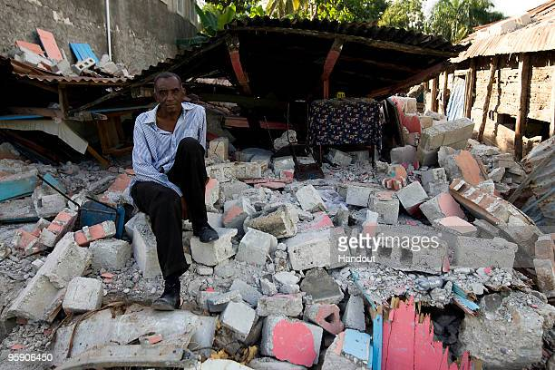 In this handout image provided by the United Nations Stabilization Mission in Haiti A Haitian man sits on the rubble that was his house January 20...