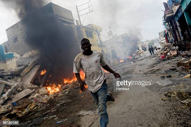 In this handout image provided by the United Nations Stabilization Mission in Haiti , A man runs besides a fire in downtown on January 25, 2010 in...