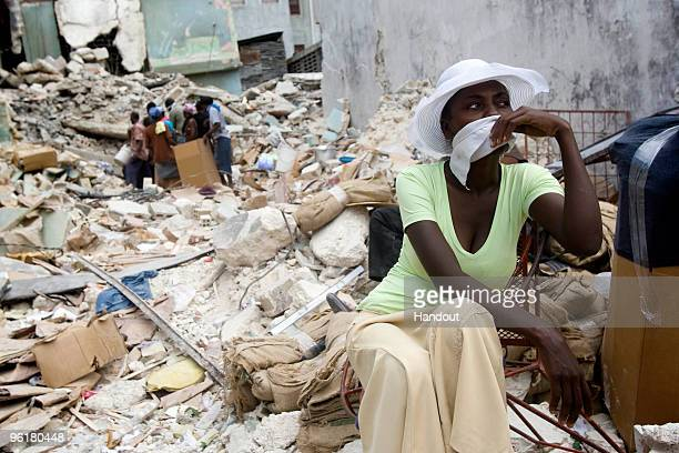 In this handout image provided by the United Nations Stabilization Mission in Haiti , A woman sits among rubbles while others try to get a way into a...