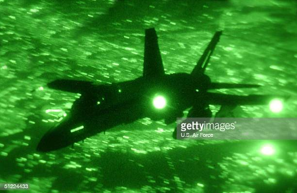 In this handout image provided by the US Air Force an F/A18 silhouetted by the lights of Baghdad flies a combat mission in support of Operation Iraqi...