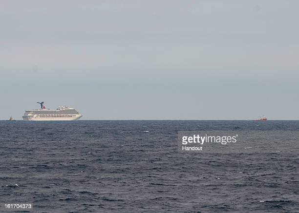 In this handout image provided by the US Coast Guard The Carnival Cruise Ship Triumph is towed by the tugboats Pioneer and Roland Falgout toward...