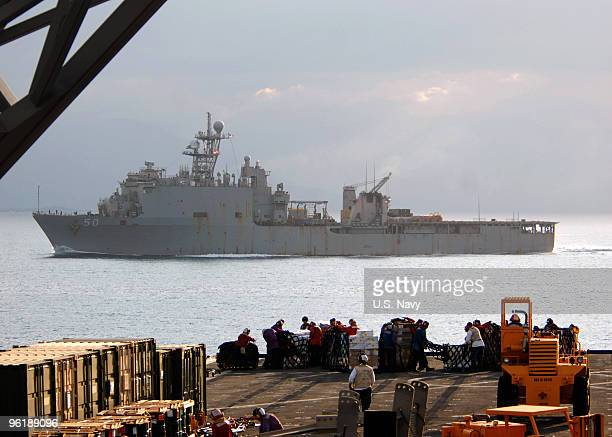 In this handout image provided by the US Navy ailors and Marines onload stores and relief supplies aboard the amphibious dock landing ship USS Fort...