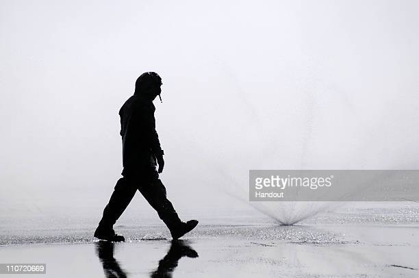In this handout image provided by the US Navy Aviation Boatswain's Mate 3rd Class Emmanuel Gedeon from Miami checks sprinklers during a...