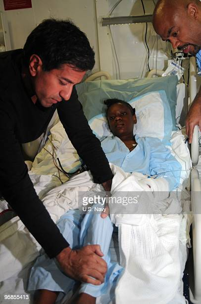 In this handout image provided by the US Navy Cmdr Dr Sanjay Gupta examines an injured Haitian girl in the medical facility aboard the Nimitzclass...