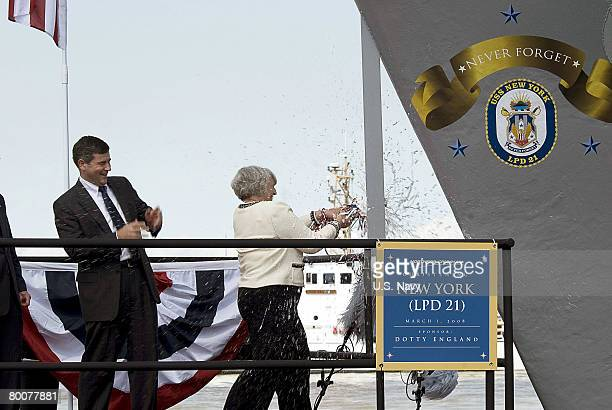 In this handout image provided by the U.S. Navy, Dorthy England wife to Deputy Secretary of Defense Gordon England breaks open a bottle of champagne...