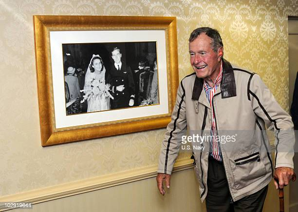 In this handout image provided by the US Navy former President George HW Bush walks past a portrait of himself and wife Barbara aboard the aircraft...