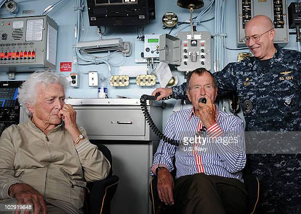 In this handout image provided by the US Navy former President George HW Bush speaks to sailors via the ship's announcing system onboard the aircraft...
