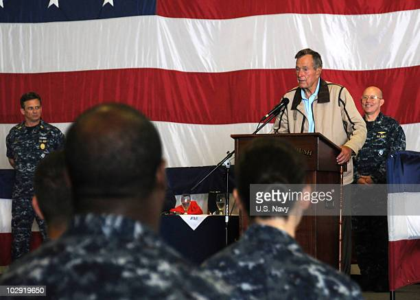 In this handout image provided by the US Navy former President George HW Bush speaks to officers and crew assigned to the aircraft carrier that bears...