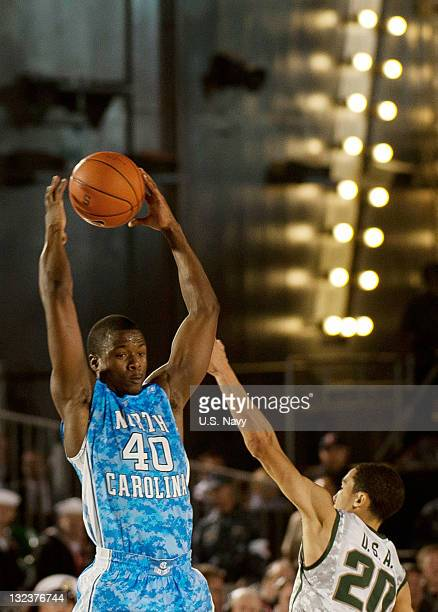 In this handout image provided by the U.S. Navy, Harrison Barnes of University of North Carolina guards the ball during the Quicken Loans Carrier...