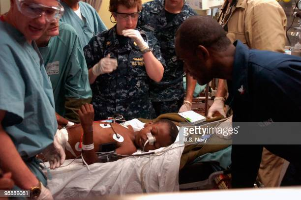 In this handout image provided by the US Navy medical professionals treat a sixyearold Haitian boy in the casualty receiving room aboard the 1000bed...