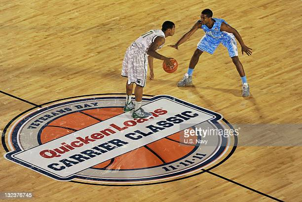 In this handout image provided by the U.S. Navy, Michigan State University guard Keith Applinging and North Carolina guard Dexter Strickland square...