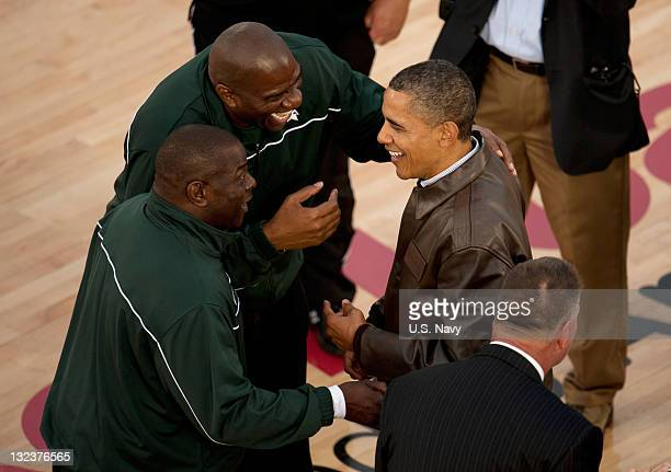In this handout image provided by the US Navy President Barack Obama is greeted on the court by NBA Hall of Fame basketball player Earvin 'Magic'...