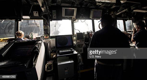 In this handout image provided by the US Navy Sailors stand watch on the bridge while Tomahawk cruise missiles are launched aboard the guidedmissile...