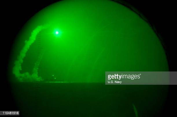 In this handout image provided by the US Navy seen through nightvision lenses aboard amphibious transport dock the USS Ponce the USS Barry fires...