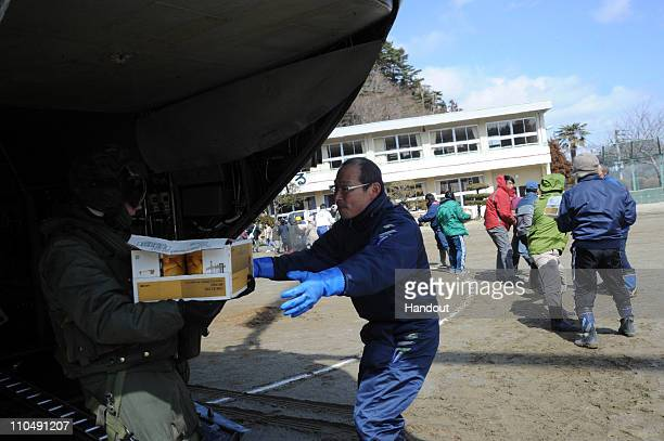 In this handout image provided by the US Navy Sgt James Ryan from Marine Medium Helicopter Squadron 265 passes a box of food to a volunteer March 18...
