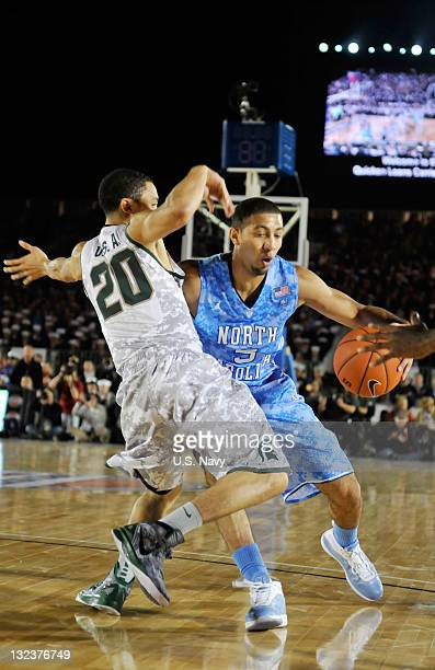 In this handout image provided by the U.S. Navy, University of North Carolina guard Kendall Marshall drives the ball against Michigan State guard...
