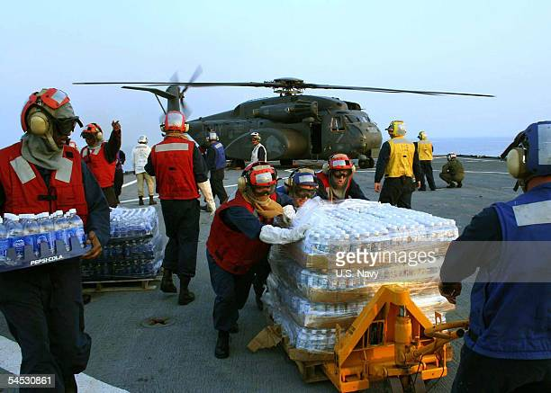 In this handout image provided by the US Navy US Navy flight deck personnel take part in an emergency replenishment working party aboard the dock...
