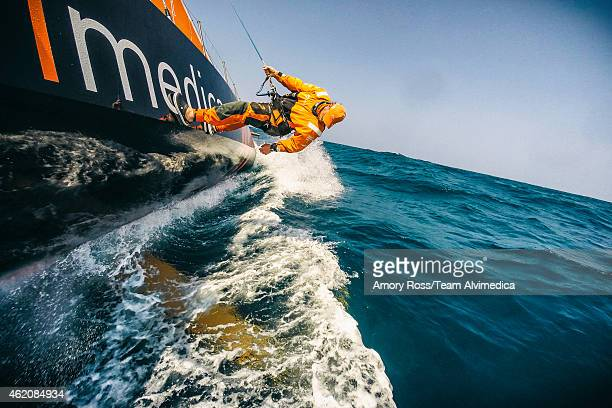 In this handout image provided by the Volvo Ocean Race Dave Swete checks for debris on the keel after sailing through a current line full of trash...