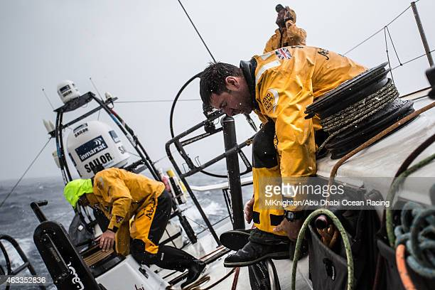 In this handout image provided by the Volvo Ocean Race onboard Abu Dhabi Ocean Racing Simon SiFi Fisher seals his trousers as the deluge of rain...