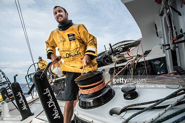 In this handout image provided by the Volvo Ocean Race onboard Abu Dhabi Ocean Racing Phil Harmer grinds and trims the barber hauler at the same time...