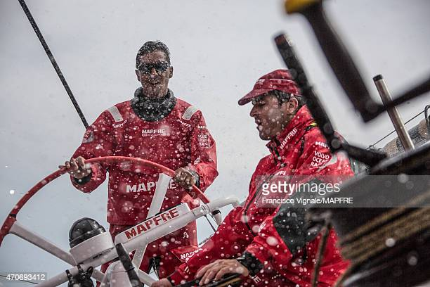 In this handout image provided by the Volvo Ocean Race onboard MAPFRE Andre Fonseca and Carlos Hernandez on watch with some spray from the reaching...