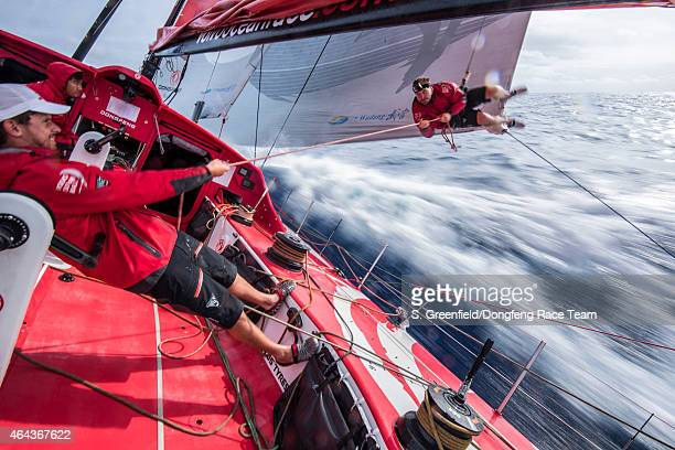 In this handout image provided by the Volvo Ocean Race onboard Dongfeng Race Team Kevin Escoffier is done checking the leech line so Thomas Rouxel...