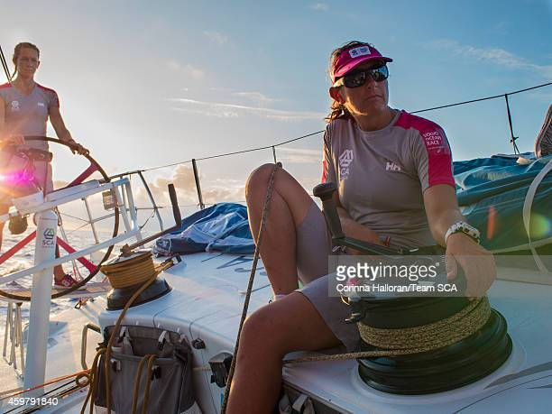 In this handout image provided by the Volvo Ocean Race onboard Team SCA Sophie Ciszek helms as Dee Caffari trims the traveler just before sunset...