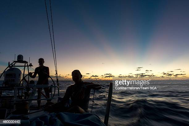 In this handout image provided by the Volvo Ocean Race onboard Team SCA Sophie Ciszek helms at sunset while Dee Caffari trims the A3 during Leg 2...