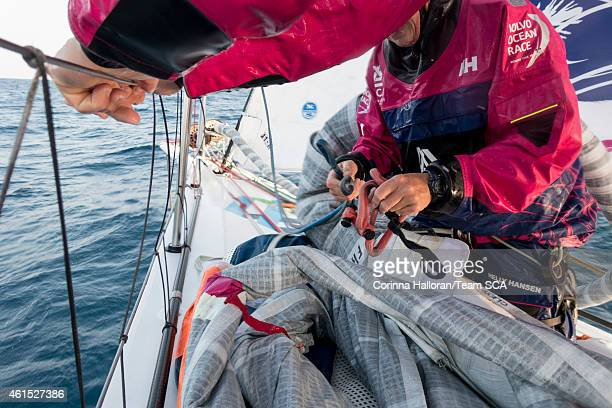 In this handout image provided by the Volvo Ocean Race onboard Team SCA Stacey Jackson adds the sheets to the FR0 in preparation for a sail change...