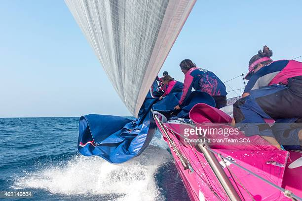 In this handout image provided by the Volvo Ocean Race onboard Team SCA The girls run to the bow to help pull in the J1 after peeling to the FR0...